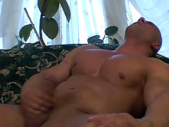 Big tan dude is jerking off on that green couch and cum